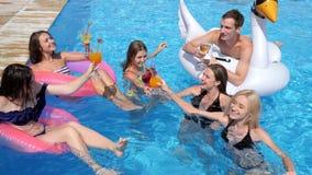 Het bedrijf van de poolpartij van de jeugd op opblaasbare ringen met alcoholische dranken rust in Poolside op de zomervakanties stock footage