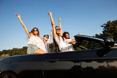Het bedrijf van jonge vrouwen en de kerels zitten in zwarte cabriolet en houden hun handen op een zonnige dag omhoog stock foto's