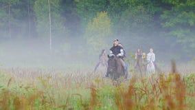 Het bedrijf van jongeren op horseback in aard lopen, die rondom de mist stock footage