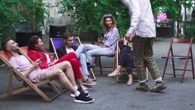 Het bedrijf van jongeren rust op een de zomergebied in een koffie stock videobeelden