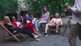 Het bedrijf van jongeren rust op een de zomergebied in een koffie stock footage