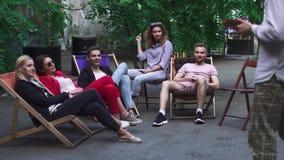 Het bedrijf van jongeren rust op een de zomergebied in een koffie stock video