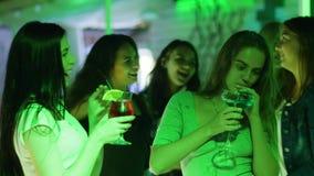 Het bedrijf van meisjes drinkt gekleurde cocktails en dans op kip-partij bij nachtclub stock video