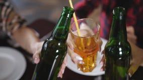 Het bedrijf van mooie meisjes in de pizzeria die flessen bier, Close-up clinking stock video
