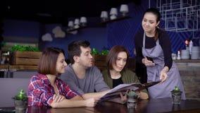 Het bedrijf van volwassen vrienden maakt een orde voor het menu in het restaurant, die naar het serveerstermeisje verwijzen, vrie stock videobeelden
