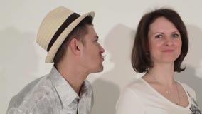 Het bedrijf van vrienden, de gelukkige vrouw in witte kleding en de aantrekkelijke mannen in hoed dansen stock footage