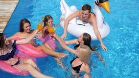 Het bedrijf van vrienden op iInflatable ringen met cocktails in handen heeft pret in pool stock footage