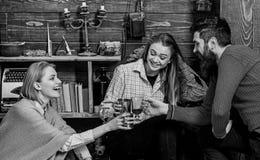 Het bedrijf van vrienden viert met overwogen wijn in comfortabele atmosfeer, houten achtergrond Juicht concept toe Vrienden die s royalty-vrije stock foto