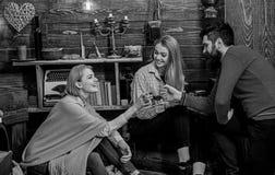 Het bedrijf van vrienden viert met overwogen wijn in comfortabele atmosfeer, houten achtergrond Mens en dames op vrolijke gezicht stock afbeelding