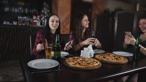 Het bedrijf van vrolijke meisjes in de pizzeria Meisje die een selfie met een smartphone in de pizzeria doen stock footage