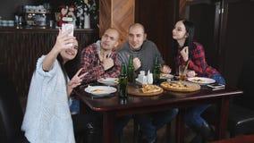 Het bedrijf van vrolijke vrienden in de pizzeria Meisje die een selfie met een smartphone in de pizzeria doen stock footage