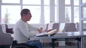 Het bedrijfs freelance, succesvolle ziekelijke mannetje op wielstoel gebruikt moderne computertechnologie voor het verre werk aan stock videobeelden
