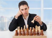Het bedrijfs mens spelen schaak, dat de beweging maakt Royalty-vrije Stock Afbeelding