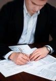 Het bedrijfs mensen invullen documenteert op een bureau. Stock Foto's