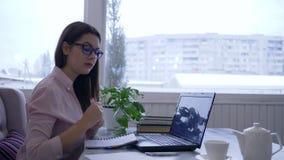 Het bedrijfs online, mooie meisje in oogglazen die laptop met behulp van en schrijft nota's met rode teller in notitieboekjezitti stock video