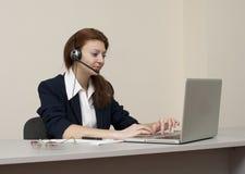 Het bedrijfs vrouwenwerk aangaande laptop in hoofdtelefoon Stock Fotografie