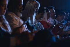 Het bedrijfscollega ontspannen in het auditorium terwijl het houden van hun smartphones royalty-vrije stock afbeeldingen