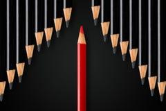 Het bedrijfsconcept verstoring, leiding of denkt diiferent; rode potlood het verdelen rij van zwarte potloden in tegenovergesteld royalty-vrije stock foto's