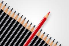Het bedrijfsconcept verstoring, leiding of denkt diiferent; rood potlood in rij van zwarte potloden die duidelijk uitkomen royalty-vrije stock fotografie