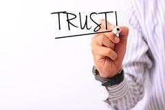 Het bedrijfsdieconceptenbeeld van een teller van de handholding en schrijft vertrouwen op wit wordt geïsoleerd Stock Afbeeldingen