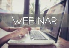 Het bedrijfshand typen op een laptop toetsenbord met Webinar-homepage stock fotografie