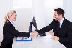 Het bedrijfsman en vrouwen schudden handen Stock Foto