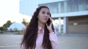 Het bedrijfsmeisje loopt rond de stad en spreekt op de telefoon 4K stock videobeelden