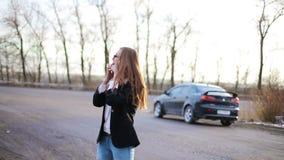 Het bedrijfsmeisje spreekt telefonisch in de werf dichtbij de auto stock video