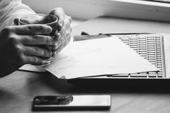 Het bedrijfsmens drinken koffie en het gebruiken van laptop zwart-witte computer Stock Foto