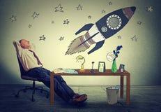 Het bedrijfsmens ontspannen bij zijn bureau in bureaudagdromen van ruimtetoerisme Royalty-vrije Stock Afbeeldingen