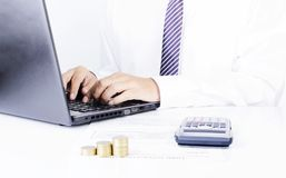 Het bedrijfsmens typen laptop met calculator en muntstukkenstapel van stock fotografie