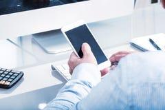 Het bedrijfsmens typen op mobiel apparaat, bureaumilieu Stock Foto's