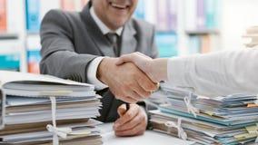 Het bedrijfsmensen schudden dient het bureau in royalty-vrije stock afbeelding