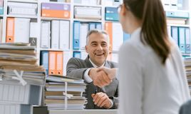 Het bedrijfsmensen schudden dient het bureau in stock foto