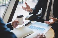 Het bedrijfsmensenteam bespreekt en analyserend op vergadering aan de planning van investeringsproject het werken en presentaties stock foto