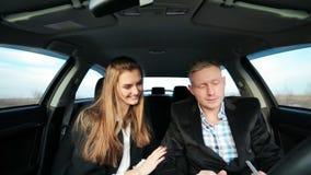Het bedrijfspaar kussen in de auto stock footage