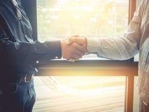 Het bedrijfsvrouw en partner schudden dient bureau in Wijnoogst filt royalty-vrije stock foto