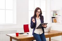 Het bedrijfsvrouw neerschrijven neemt van op kantoor nota Stock Foto's
