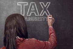 Het bedrijfsvrouw schrijven fiscale amnestiecitaten stock foto's