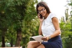 Het bedrijfsvrouw schrijven nota's die door mobiele telefoon spreken royalty-vrije stock foto