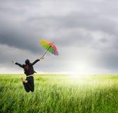 Het bedrijfsvrouw springen de paraplu van de holdingsregenboog in groene padievelden en raincloud Royalty-vrije Stock Fotografie