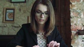 Het bedrijfsvrouw werken met een tablet en verheugt zich plotseling in koffie 4K stock footage