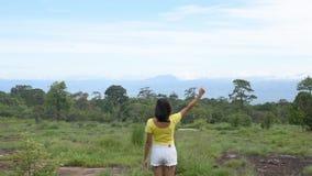 Het beeld achter de vrouwen heft hun wapens op bekeek de bergen en de bomen bij het Nationale Park van Phu Hin Rong Kla, Phetchab stock video
