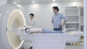 Het beeld hoofdaftasten van de klinieknoodsituatie MRI voor het leggen van de mens stock video