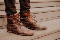 Het beeld van bemant bruin schoeisel die zich op houten stappen bevinden Mannetje in broeken en ruwharige schoenen op drempel Hor stock foto's