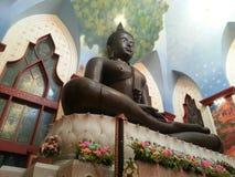 Het beeld van Boedha dat met bloemen in mooie kerk wordt verfraaid Stock Foto's
