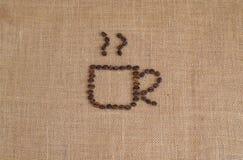 Het beeld van de koffiekop uit koffiebonen wordt samengesteld op juteachtergrond die Stock Foto's