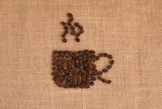 Het beeld van de koffiekop uit koffiebonen wordt samengesteld op juteachtergrond die Stock Afbeeldingen