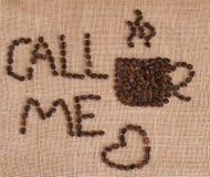 Het beeld van de koffiekop uit koffiebonen wordt samengesteld op juteachtergrond die Royalty-vrije Stock Afbeeldingen