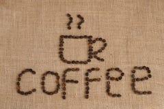 Het beeld van de koffiekop uit koffiebonen wordt samengesteld op juteachtergrond die Royalty-vrije Stock Foto